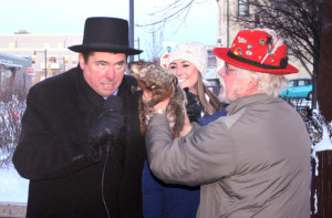 Then-mayor Jon Freund, left, leans in for Jimmy the Groundhog's prognostication on Feb. 2, 2015 -- just before he was famously bitten on the ear by the groundhog during Sun Prairie's Groundhog Day celebration.  The roots of Groundhog Day date back to the 6th century.  (Photo credit:  Associated Press)