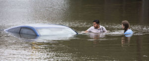 "Roberto Salas, left, and Lewis Sternhagen check a flooded car in Houston on May 26. This spring the Houston area has experienced five separate rain events that have been classified as ""once in a hundred year"" events, which have a 1 percent chance (or a 1-in-a -100 chance) of occurring in any given year. (Photo credit: Associated Press)"