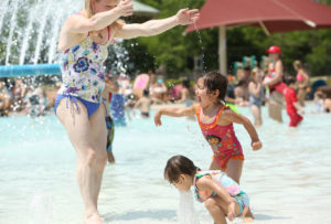 Jennifer Ronquillo, of Madison, plays with her daughters at opening day at the Goodman Pool on June 10 -- Madison's first 90-degree day of the year and the third day of a record-shattering 110-day streak of temperatures at or above 70 degrees. (Photo credit: Amber Arnold, State Journal)