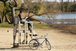 Alvaro Ceballos enjoys November's mild weather as he stops to read at Vilas Beach on Lake Wingra on his way home from getting a haircut. Madison averaged 7.6 degrees above normal for the month, which ranked as the third warmest November on record. (Photo credit: Amber Arnold, State Journal)